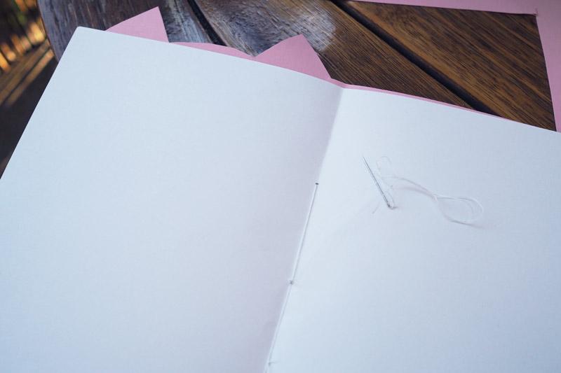 Den Umschlag des Schweine-Notizheftes annähen
